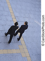 Business partners - Two businessmen walking in a citySlighty...