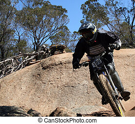 Mountain Bike - extreme mountain biker jumping a large rock