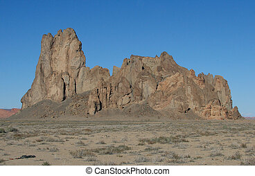 Desert Outcrop - Huge outcropping of rock looms above the...