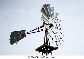Windmill, shot against blue sky, generates power to pump...