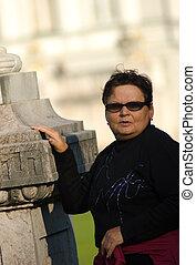 woman - elderly woman stands beside sculpture