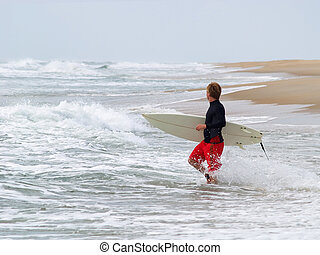 Lone Surfer - Young man with surfboard wades into the water...