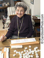 senior woman at the game table - happy senior woman playing...