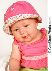 Baby Hat - A baby girl sitting with a hat on her head