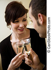 cheers - young couple celebrating some occasion and having...