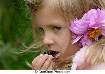the little girl with a flower in hair eats a blackberry