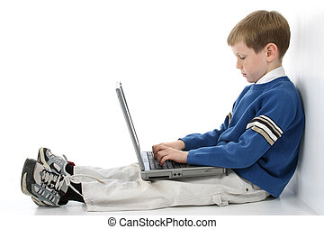 Boy on Laptop - Adorable eight year old boy working on...
