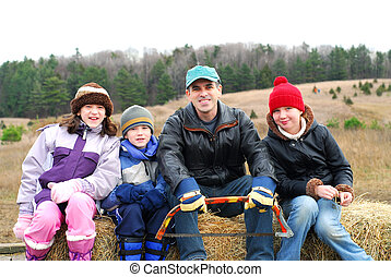 Family sitting on a vagon on Christmas tree farm