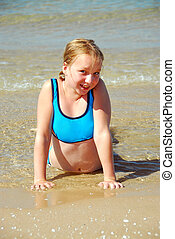 Girl beach - Young girl lying on a beach in shallow water