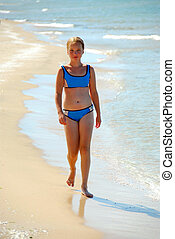 Girl beach - Young walking on a beach in shallow water