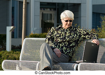 woman with laptop - elderly woman on bench with laptop