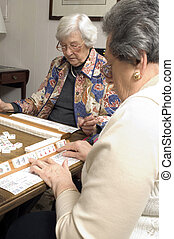 senior woman at the game table - happy senior women playing...