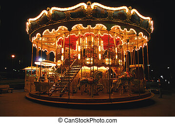 Carousel - Brightly illuminated traditional carousel in...