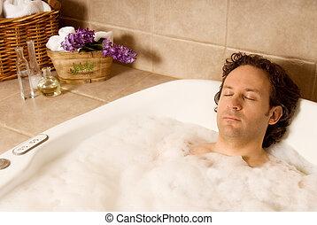 man in bath - man client getting a bubble bath at spa