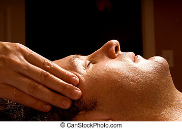 Facial - man getting a massage facial from therapist