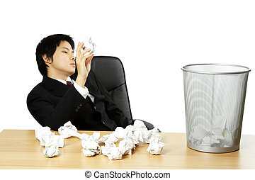 Stressed businessman - A businessman throwing trash into a...