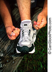Tieing Shoe - Man tieing athletic shoe showing only shoe and...