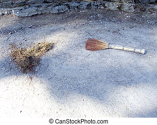 Broom and dust on sidewalk