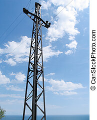 Electric mast on a background of the sea and the blue sky