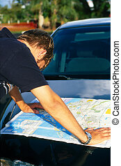 Directions - Man looking at a map on hood of car