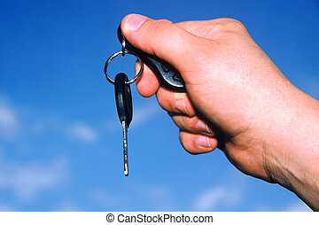 Car Keys - Hand holding car key against a blue sky
