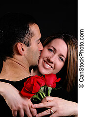 happiness - A woman hugging her husband holding roses