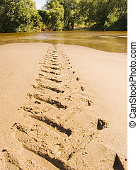 Trace of a tractor on river sand