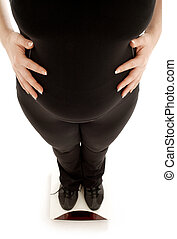 pregnant lady weighing oneself, focus on belly - lovely...
