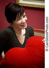 smiling girl - girl holding a heart shaped pillow valentines...