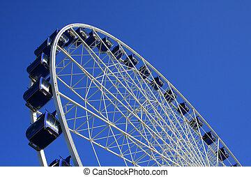 Ferris Wheel - A side view of a giant ferris wheel on a blue...