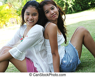 Portrait of two lovely Thai girls sitting back to back on...