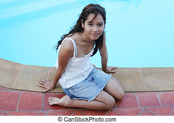 Teenager sitting by the side of the swimming pool