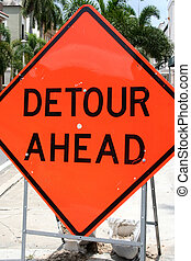 Detour Ahead - Orange detour sign in road