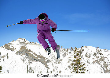 Skier jumping against the sky and mountains