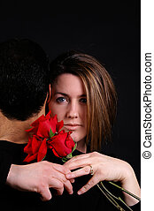 Romance - A woman hugging her husband and holding red roses