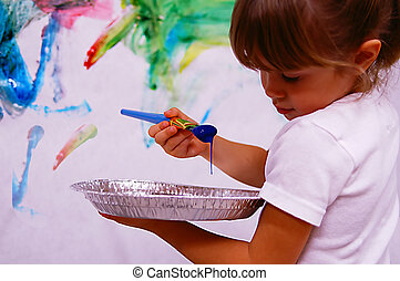 Young artist - A young girl painting on the wall