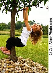 Hanging out - A young girl hanging from a tree
