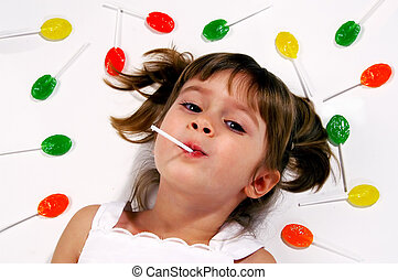 lollipops - A young girl lying on the floor with her suckers