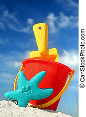 Beach Toys - Bucket and spade on tropical beach with blue...
