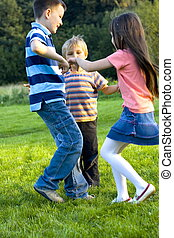 Happines - Sister with brothers dancing on a meadow