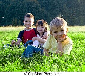 fun on a meadow - Happy children in green grass