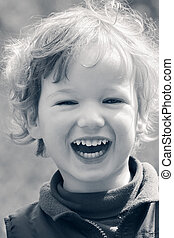 Happy laughing child - Small curly boy is cheerfully...