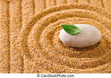Zen garden - Macro of a stone with a leaf on raked sand