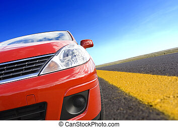 Car travel - Red car on a rural road with yellow line