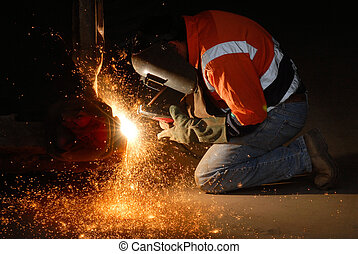 Welding Sparks - Worker welding steel at an engineering...