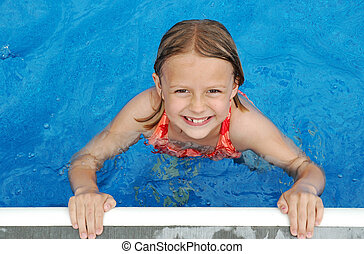 Poolside Smile - Young girl looks up from the pool with a...