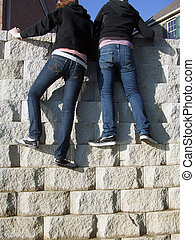 Escape - two teens in jeans climbing a stone wall
