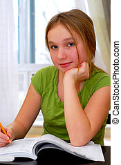 School girl - Young school girl doing homework at her desk