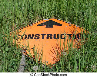 Construction Detour - Construction sign lying in a grassy...