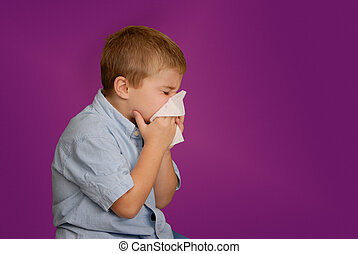 Boy blowing nose - Young boy with tissue up to his nose